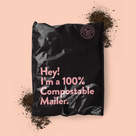 "A black noissue compostable mailer reading ""Hey! I'm a 100% Compostable Mailer."" in pink text on a pink background with 2 piles of soil."