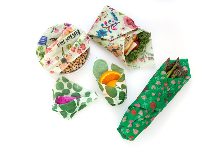 Cereal bowl, asparagus, orange, and a sandwich each covered with reusable beeswax wraps, in green leaf and pod patterns