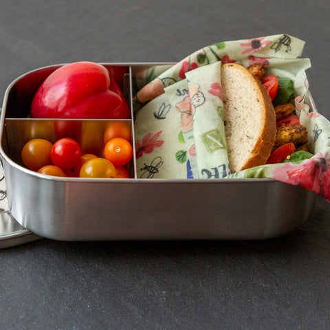 A sandwich wrapped in Bees Love These sits in a divided stainless steel lunch tin with cherry tomatoes and a nectarine.