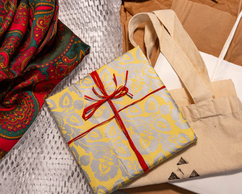 A mix of alternatives to wrapping paper: brown craft paper, recycled papers, raffia ribbon, paper and cloth bags, and a wrapping cloth