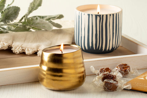 a blue and white striped candle with a gold candle from Prosperity Candle and some caramel candies on a white wood tray