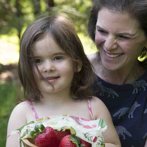 Michelle Zimora and her daughter, holding a bowl of strawberries covered partly with a Farmer's Market print Z Wrap