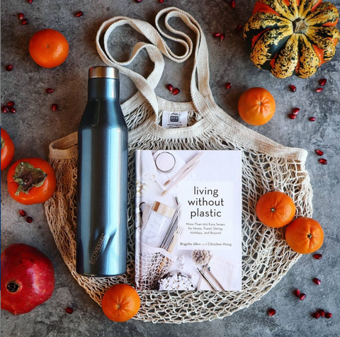 Living Without Plastic book cover on a cotton grocery bag with orange fruits and a blue metal reusable water bottle