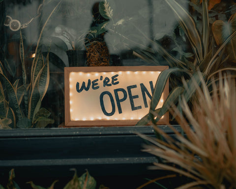 A sign in a window partially obscured by plants that reads We're Open