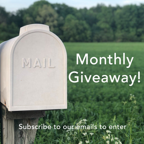 A white mailbox reading MAIL on the door against a green field in the background. Text reads: Monthly Giveaway! Subscribe to our emails to enter.