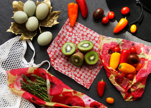 A spread of farmers' market goodies on a dark slate surface: blue tinted eggs, red orange and yellow sweet peppers, cut kiwis, and asparagus in various Z Wraps. A shopping bag and sun hat peek out from opposite corners.