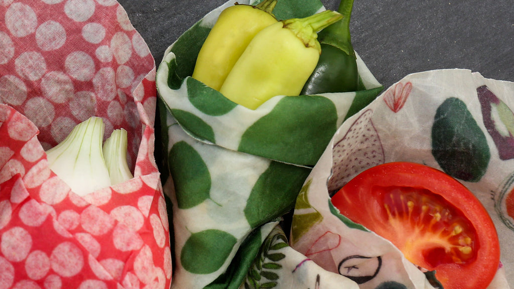 closeup of three veggie friends wrapped side by side: onion in connect the dots wrap, some green chilis in a leafy green wrap, and half a tomato in the farmer's market wrap