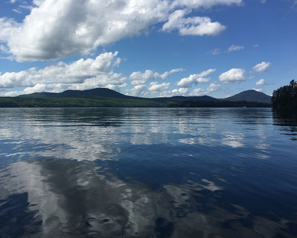 Blue skies and puffy white clouds reflected in a calm lake surface, with mountains in the distance.