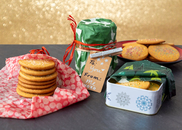 "Sugar cookies being prepped for gifting in front of a sparkly gold background. left to right, a stack of cookies on a dot-print wrap, a wrapped cylinder of cookies in a leafy green wrap with a red raffia ribbon and ""from me to you"" gift tag, a plate of cookies in the background, and a snowflake-print tin of cookies with a winter trees wrap."