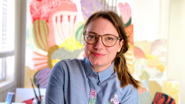 Illustrator Katie Vernon pictured in her colorful studio with her paintings behind her in the background