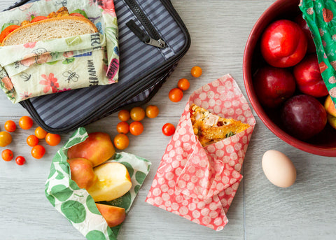 Lunch items- a sandwich, apple slices, and a piece of pizza- wrapped in Z Wraps; they sit on a PackIt lunch bag next to a maroon bowl of nectarines