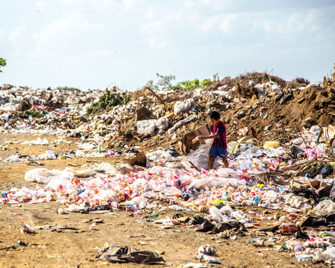 plastic pollution surrounds a small child under a hazy sky