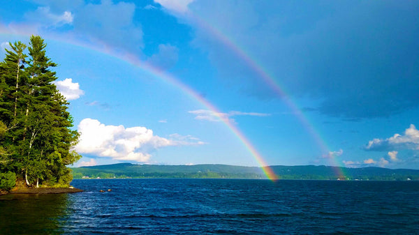 A double rainbow over a lake, with mountains in the background