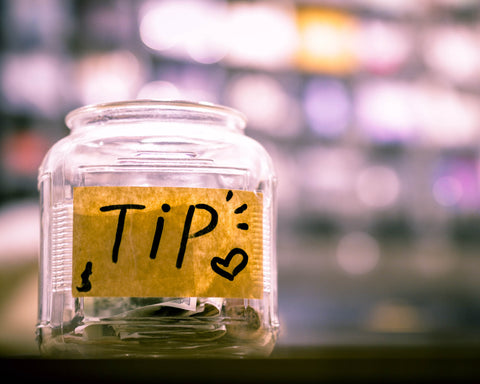 A jar with money in it and a label that reads TIP