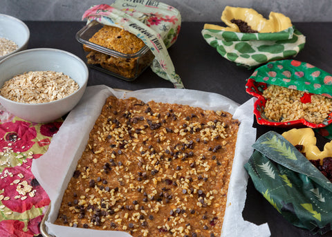 a tray of snack bars ready to bake, surrouned by ingredients and finished bars in the background