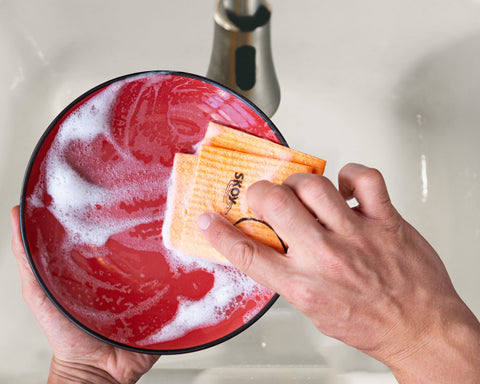 Hands with an orange Skoy Swedish Dishcloth wash a soapy red plate over a white sink.