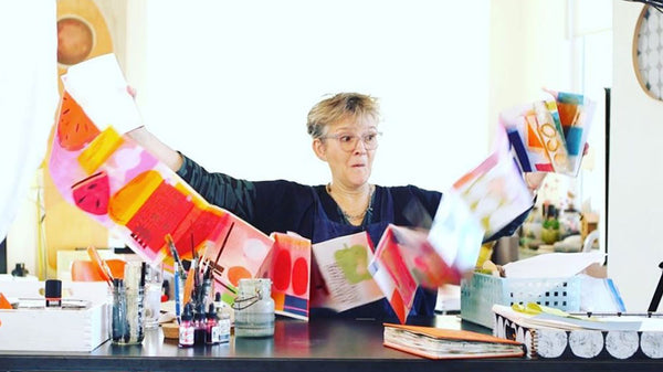 Susy Pilgrim sitting at her studio desk in her light and bright studio, excitedly holding up a bunting or garland of colorful squares