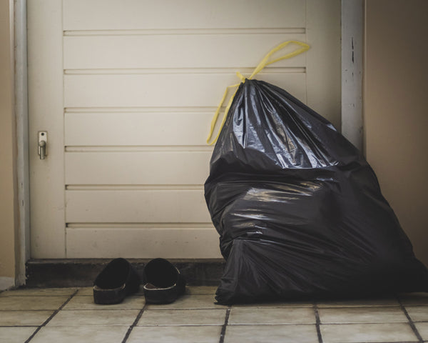 A black plastic trash bag, full, sits ominously waiting to be taken out next to a door and a pair of shoes.