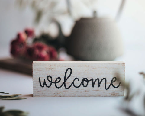 """a rustic wooden """"Welcome"""" sign in a round cursive font sits in front of a teapot and some red flowers"""