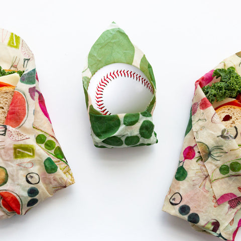 A silly picture of a baseball wrapped in a leafy green print Z Wrap, flanked by a sandwich in Farmer's Market design on the left and right