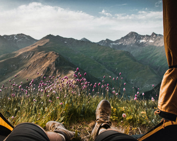 Feet looking out from a tent with purple flowers and mountains bathed in golden sunlight