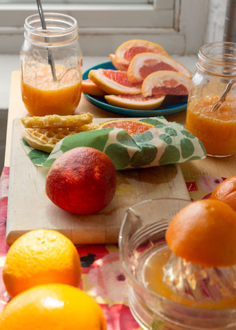 Assorted citrus slices and fresh squeezed juice; a Painted Poppy Z Wrap covers the counter, with a small Z Wraps beeswax food wrap covering half a citrus left on the cutting board
