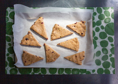 Cut, unbaked scones on parchment waiting for the oven; a Leafy Green XL Z Wrap covers the work surface under the tray