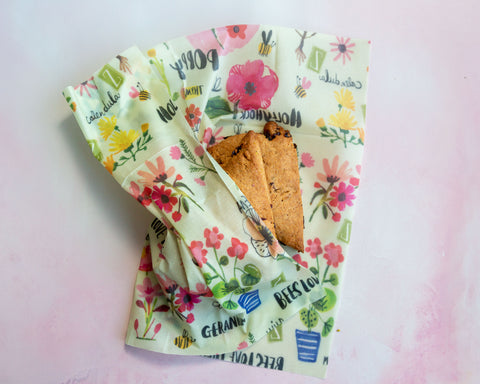 Scones without frosting rest in a Bees Love These print Z Wrap on a mottled pink surface
