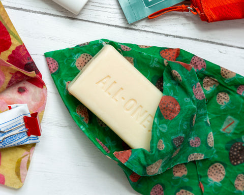 A Strawberry Fields print Z Wrap opens to reveal a bar of soap, surrounded my misc other bath items
