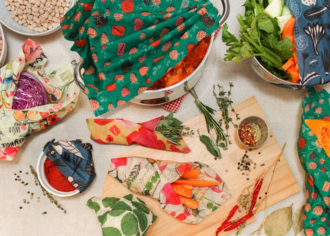 A flatlay image of the construction of a pot of shakshuka, with a variety of ingredients both wrapped and unwrapped scattered across a beige table cloth. Left to right starting at the top: A pale blue bowl of chickpeas; a pot of shakshuka mostly covered by a Strawberry Fields print wrap; a stainless steel bowl of prepped veggies sticking out from under a blue Petals and Pods print Z Wrap; next row from left: a portion of purple cabbage in a Bees Love These print wrap; a small bundle of fresh herbs in a small Painted Poppy wrap; loose herbs and spices on and around a cutting board; bottom most row from left: some loose peppercorns and a sprig of thyme next to a white ramekin of tomato paste partly covered by a blue Petals and Pods wrap; something unseen covered completely by a Leafy Green print wrap; a bunch of carrot sticks in a cone of Farmer's Market print wrap; some dried chili peppers on their branch; a loose bay leaf; half a butternut squash, insides visible, in a Strawberry Fields wrap.