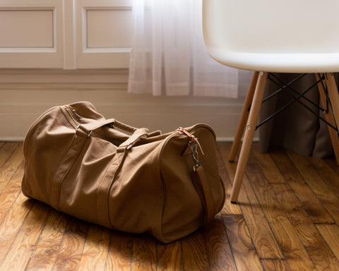 A tan duffle sits on the floor next to a white chair, ready for the next trip