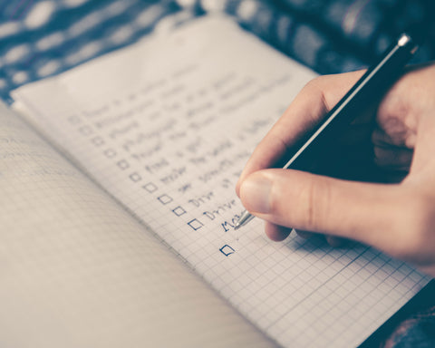 a hand uses a black pen to make a list in a small notebook