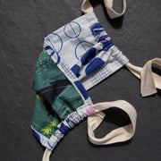 Cloth face mask with green tree print on one side and blue and white pattern on the other