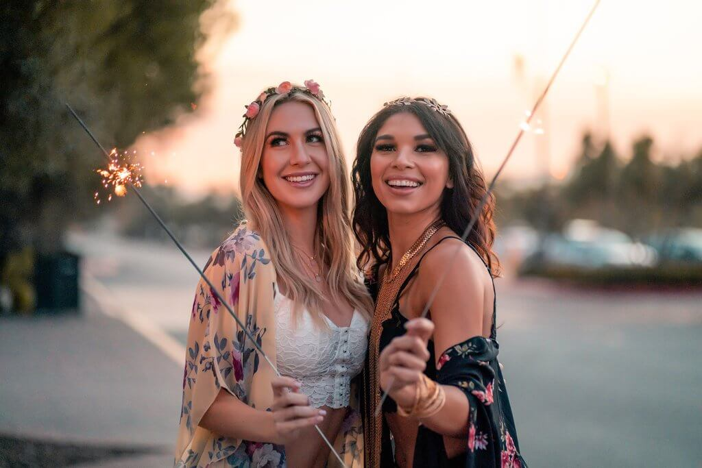 Two woman wearing floral kimonos and holding sparklers