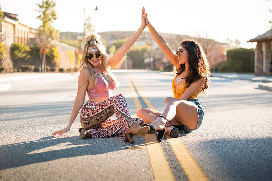 A blonde and a brunette bohemian woman sitting & smiling in the middle of the road