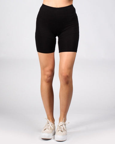 Black bike shorts with light tan sneakers