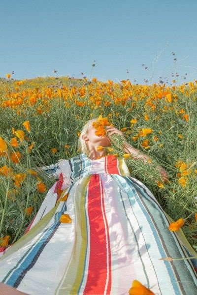 Girl in rainbow striped summer dress lying in a meadow looking up at a blue sky