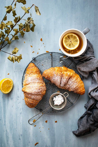 Plate of croissants and lemon tea set out on a table