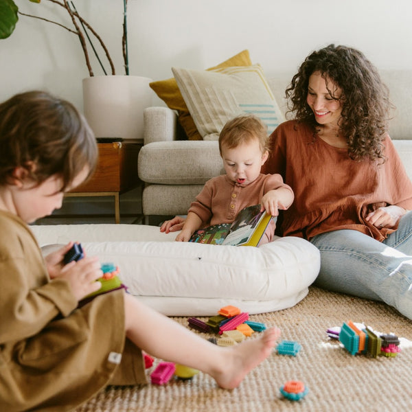 mother and children play in living room with DockATot in lockdown
