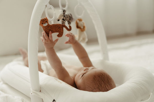 Baby lying in a DockATot Deluxe+ dock in Pristine White playing with the Toy Arch
