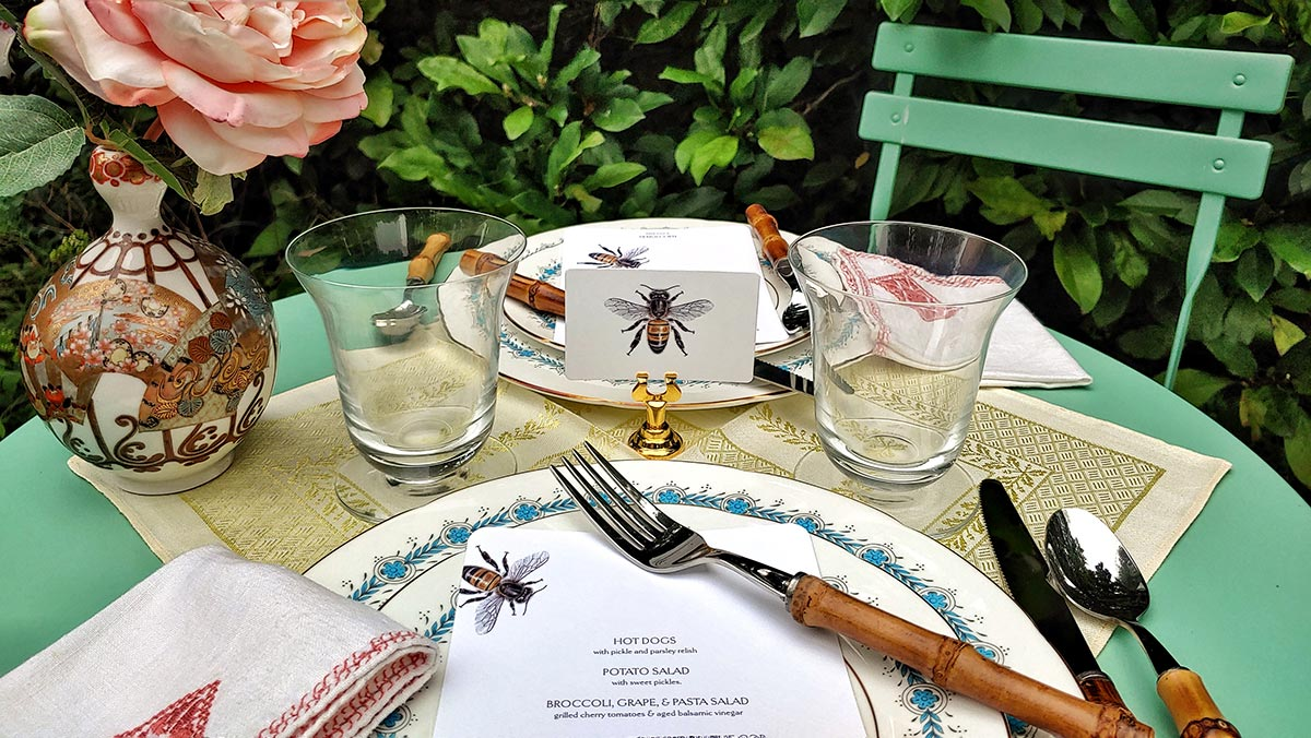 tea alfresco with green garden table for two, 'bees' illustrated place cards, bespoke menu cards, bamboo cutlery, and tea cups and bud vase