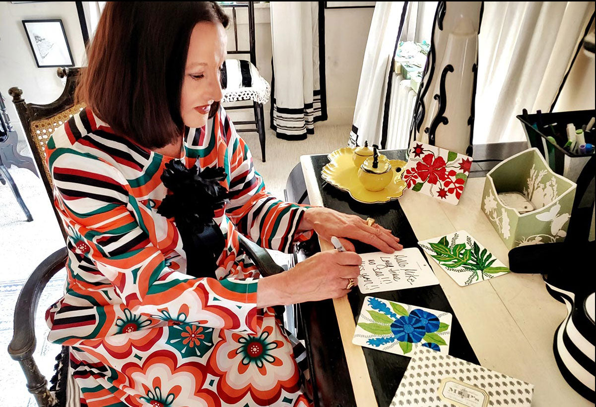 Decorative artist Marian McEvoy at her writing desk using note cards from marian mcevoy x the punctilious mr. p's place card co. wearing a beautiful floral 60s inspired dress