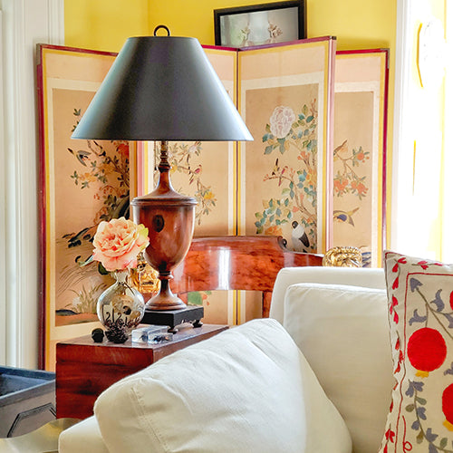 The Punctilious Mr. P's Place Card Co. Living room with antique chinoiserie screen, wooden urn table lamp, suzani pillows