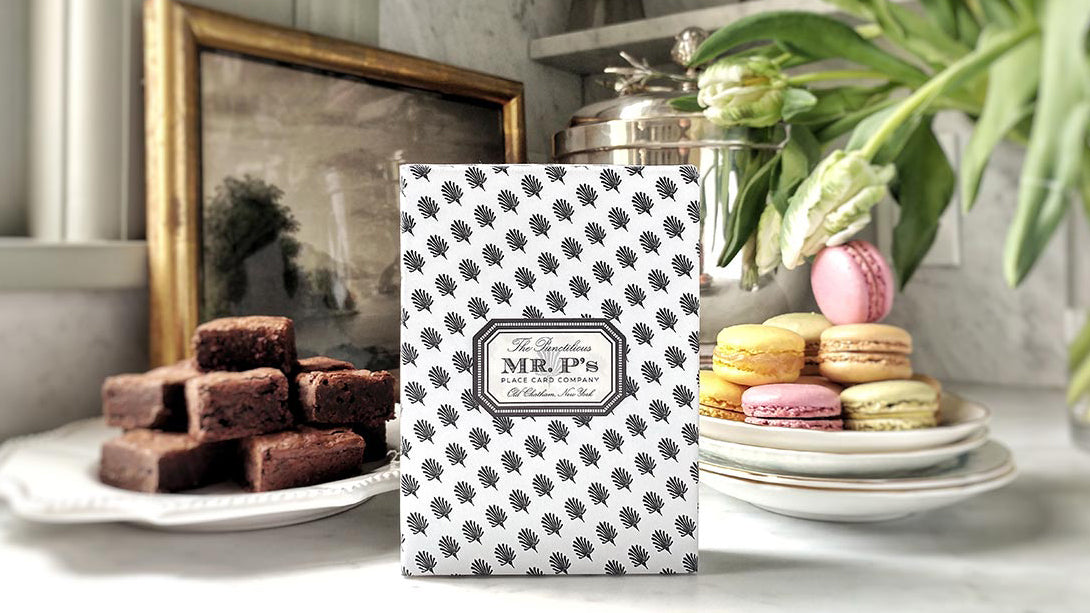 The Punctilious Mr. P's Place Card Co. gift box with macaroon and brownies in the background