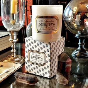 detail of the salon at B'ellow, showing Mr. P's Twilight essential oil candle and anthemion printed box on a mirrored table with crystals and antique objects