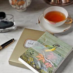 A front view of a pack of Mr. P's Note Cards in gold folio case on a marble table with cup of tea next to it