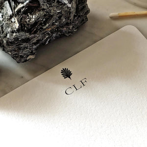 The Punctilious Mr. P's fine note card set on marble ledge with crystals on top showing personalized initials on card's marquee
