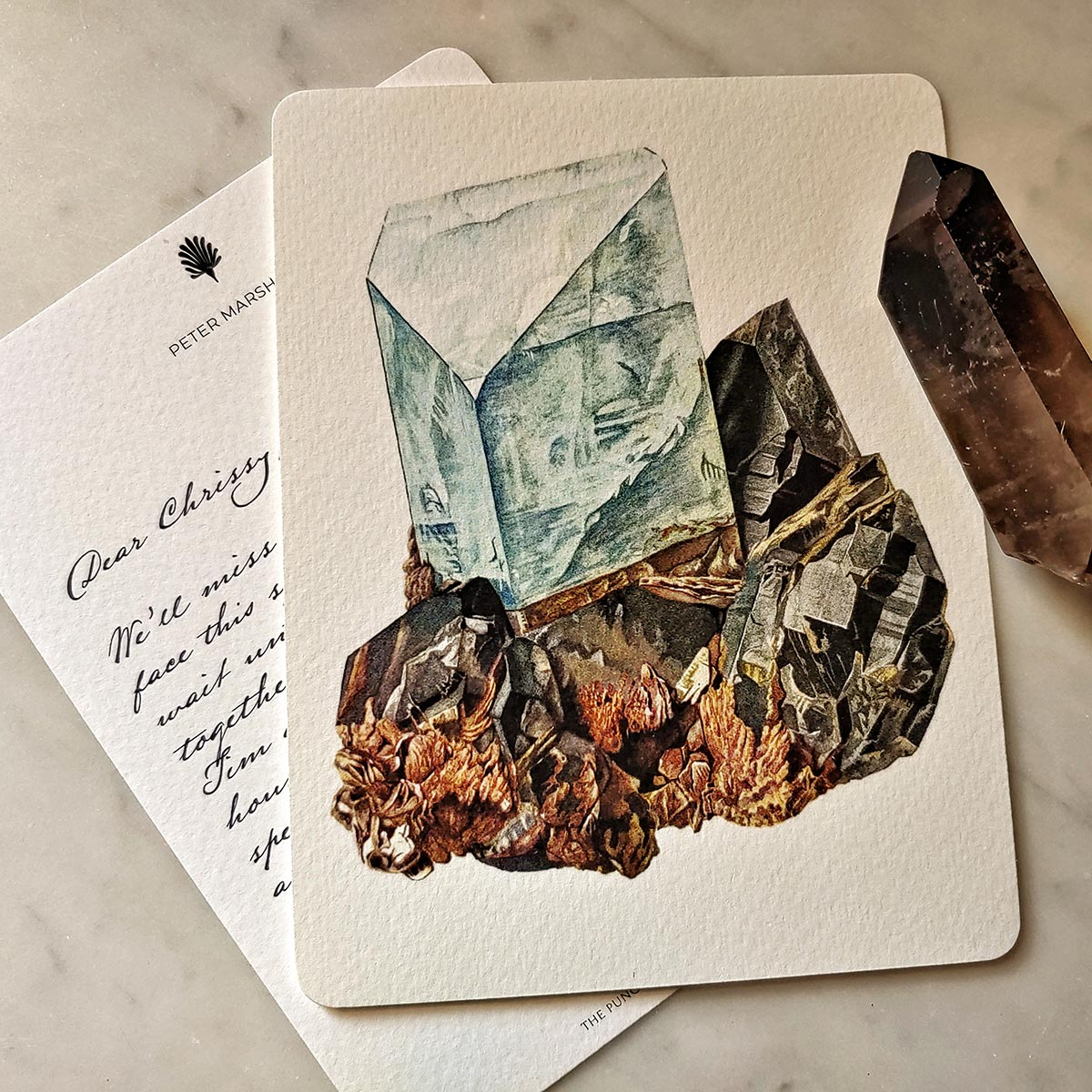 The Punctilious Mr. P's 'Minerals No. 4' fine note card on marble ledge with crystals on top showing the back of the card with digital calligraphy note