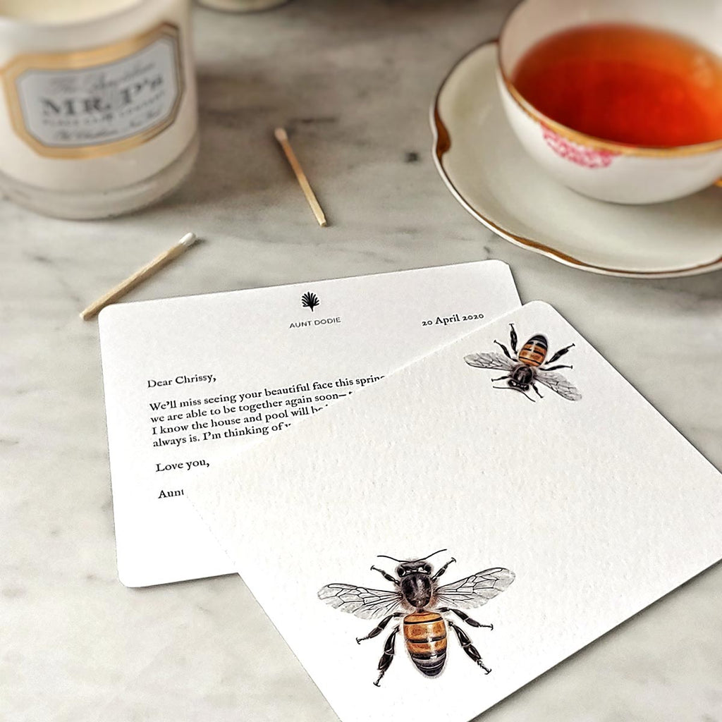 The Punctilious Mr. P's 'Bees' note cards on marble table with cup of tea and pax candle in background