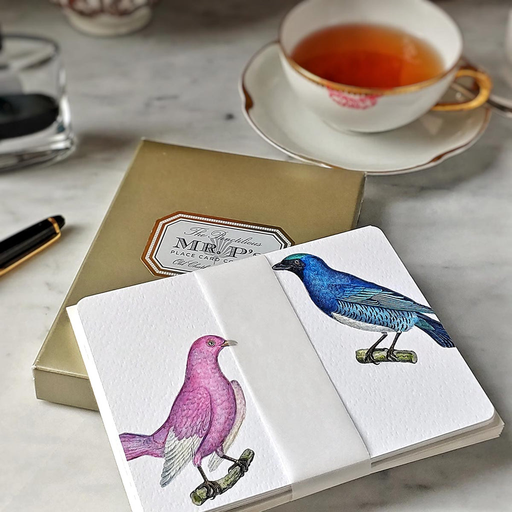 The Punctilious Mr. P's 'chromatic cuckoo' note card pack- showing pink and blue birds on top of gold folio case and cup of tea in background